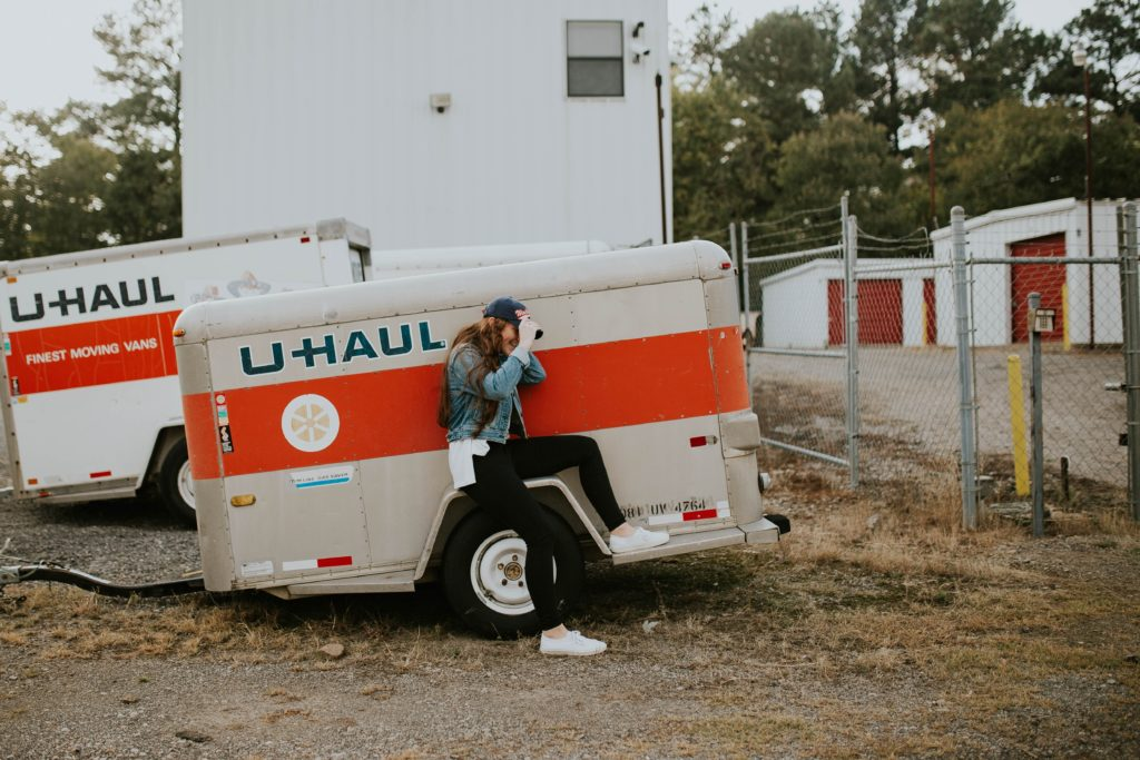 woman sitting on U-Haul trailer wheel fairings